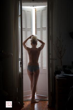 Femme devant les persiennes