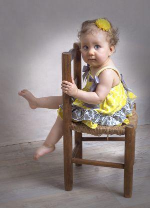 Petite fille à califourchon sur sa chaise